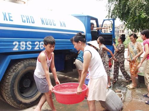 Người dân Hà Nội đi lấy nước ăn từ xe bồn trở tới. Ảnh: Hồng Vĩnh.