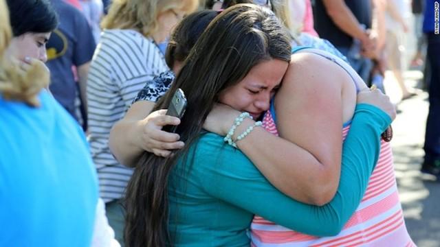 Một nữ sinh may mắn sống sót sau vụ xả súng ôm chầm lấy người thân bên ngoài khuôn viên trường. Ảnh: AP