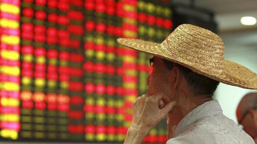 Nhà đầu tư quan sát giá chứng khoán tại Hải Khẩu, Trung Quốc 11/8/2015 Ảnh: Reuters
