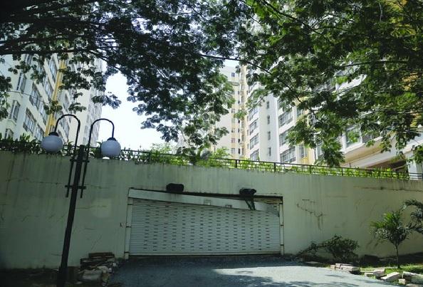 Cánh cửa sắt khu chung cư bị hư hại, tường nhiều vết nứt bị mọc rêu xanh, không được bảo trì.