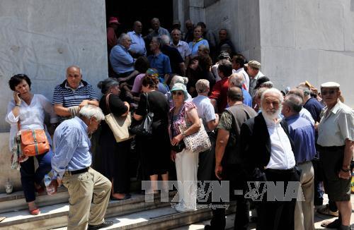 Người dân xếp hàng chờ rút tiền bên ngoài chi nhánh Ngân hàng quốc gia Hy Lạp đã đóng cửa ở Thessaloniki ngày 29/6. Ảnh: TTXVN