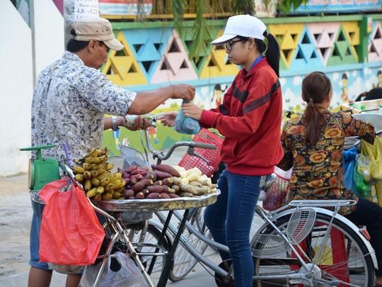 Nữ công nhân mua khoai trước giờ vào ca.ẢNH: NGUYỄN LUÂN