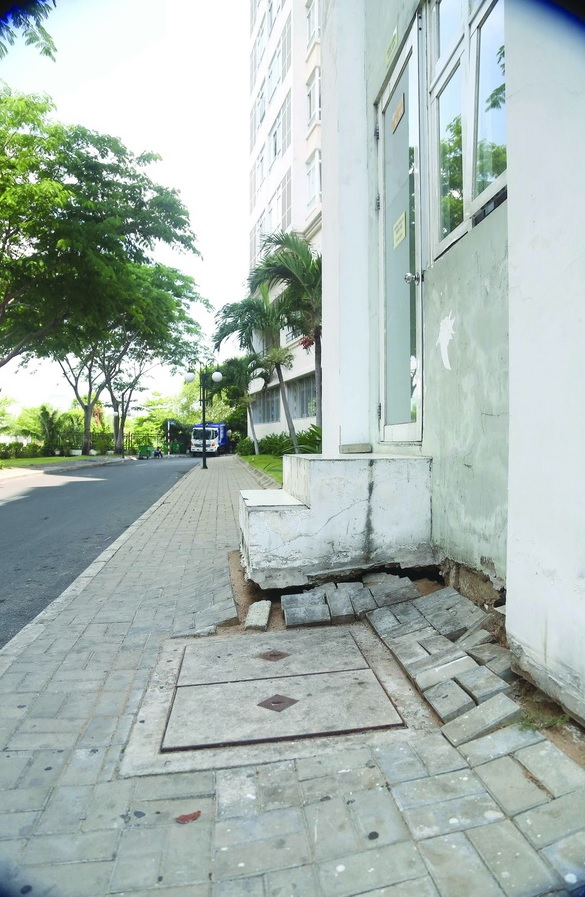 Nền gạch bị lún tạo thành lỗ hổng ngăn cách giữa nền đường và bậc thang ra vào tại khu căn hộ.