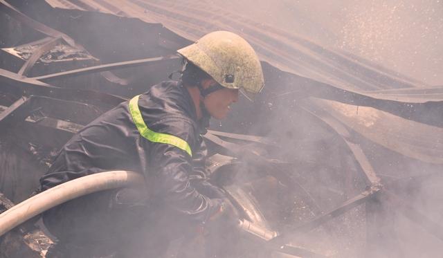 Bất chấp nguy hiểm, các chiến sĩ PCCC đã leo lên mái tôn, phun nước dồn dập vào bên trong