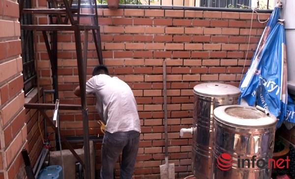 Giếng khoan của nhà bà Nguyễn Thị Huyền bên bức tường ngoài cửa.