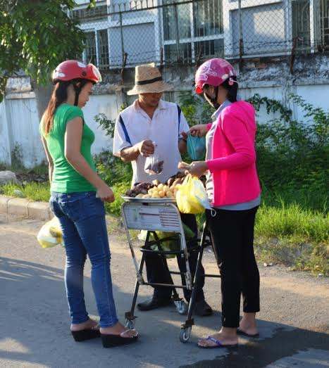 Hai nữ công nhân tranh thủ mua khoai mì trước lúc vào ca  ẢNH: NGUYỄN LUÂN