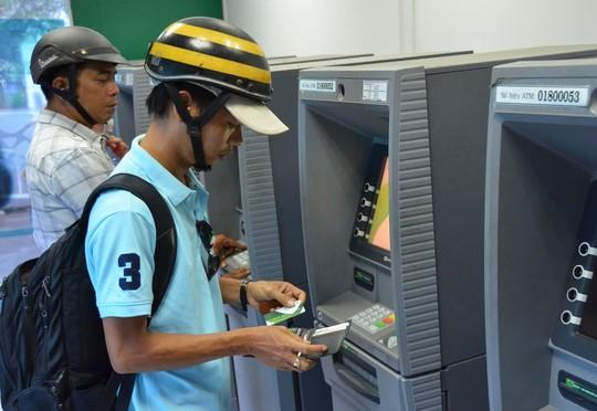 Công nhân rút tiền tại các máy ATM ở KCX Tân Thuận, TP HCM (ảnh lớn) và một máy ATM trên đường Bà Huyện Thanh Quan (quận 3) không hoạt động trong sáng 9-2 (ảnh nhỏ)Ảnh: Tấn Thạnh