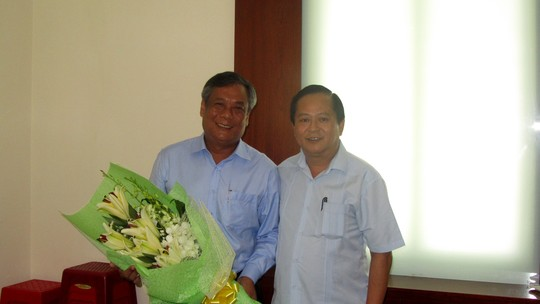 Phó Chủ tịch UBND TP HCM Nguyễn Hữu Tín (phải) trao quyết định điều động ông Nguyễn Thành Chung, Giám đốc Sở GTVT TP HCM (trái) về Quận ủy quận Tân Phú vào sáng nay (Ảnh: TĐ)