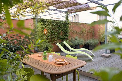 Với sàn gỗ, cây xanh và bàn ghế tông màu nâu xanh như thế này, sân thượng nhà bạn sẽ thổi bay cái nắng nóng mùa hè giữa lòng thành phố.