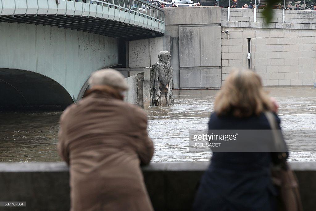 Cùng nhau ngắm nhìn nước sông dâng cao. Ảnh: Joel Saget/ AFP