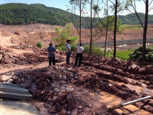Vệt bánh xe chạy nham nhở trên nền đất đá mới bị đào sới.