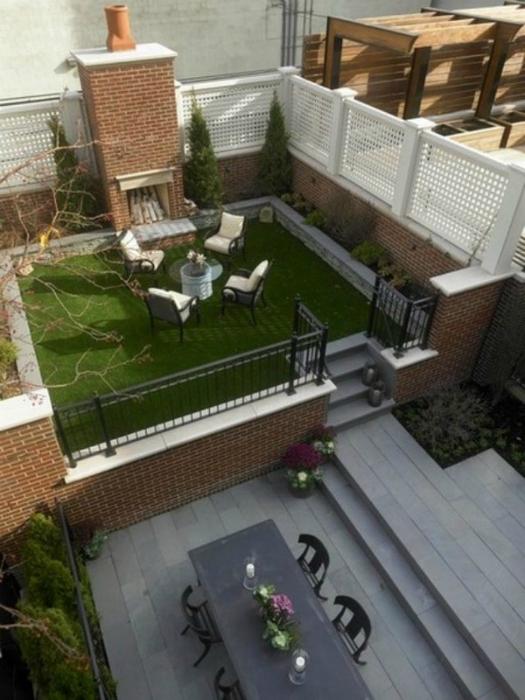 Ăn uống trên sân thượng với một bãi cỏ cắt tỉa cẩn thận và một lò sưởi lớn.