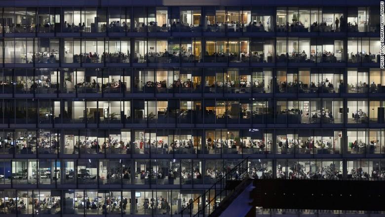 Nhân viên ngân hàng làm việc tại văn phòng vào ban đêm tại London. Ảnh CNN