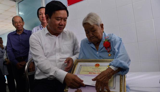 Bí thư Thành ủy TP.HCM Đinh La Thăng thăm hỏi sức khỏe mẹ Nguyễn Thị Mận sáng 5-6 - Ảnh: QUANH ĐỊNH