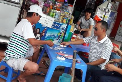"""""""Cò"""" Toàn (phải) đang chơi bài trong khi chờ khách tại quán nước cạnh Chi cục Thuế quận Cầu Giấy."""