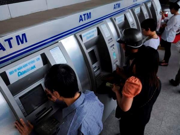 Khách hàng đang rút tiền tại ATM. (Ảnh: PV/Vietnam+)