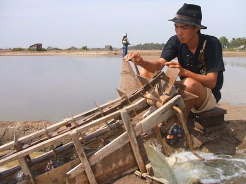 Ông Lâm Văn Mật, ấp Lang Cháo, xã Dân Thành, Duyên Hải tranh thủ lấy nước mặn vàokhuônruộng muối.