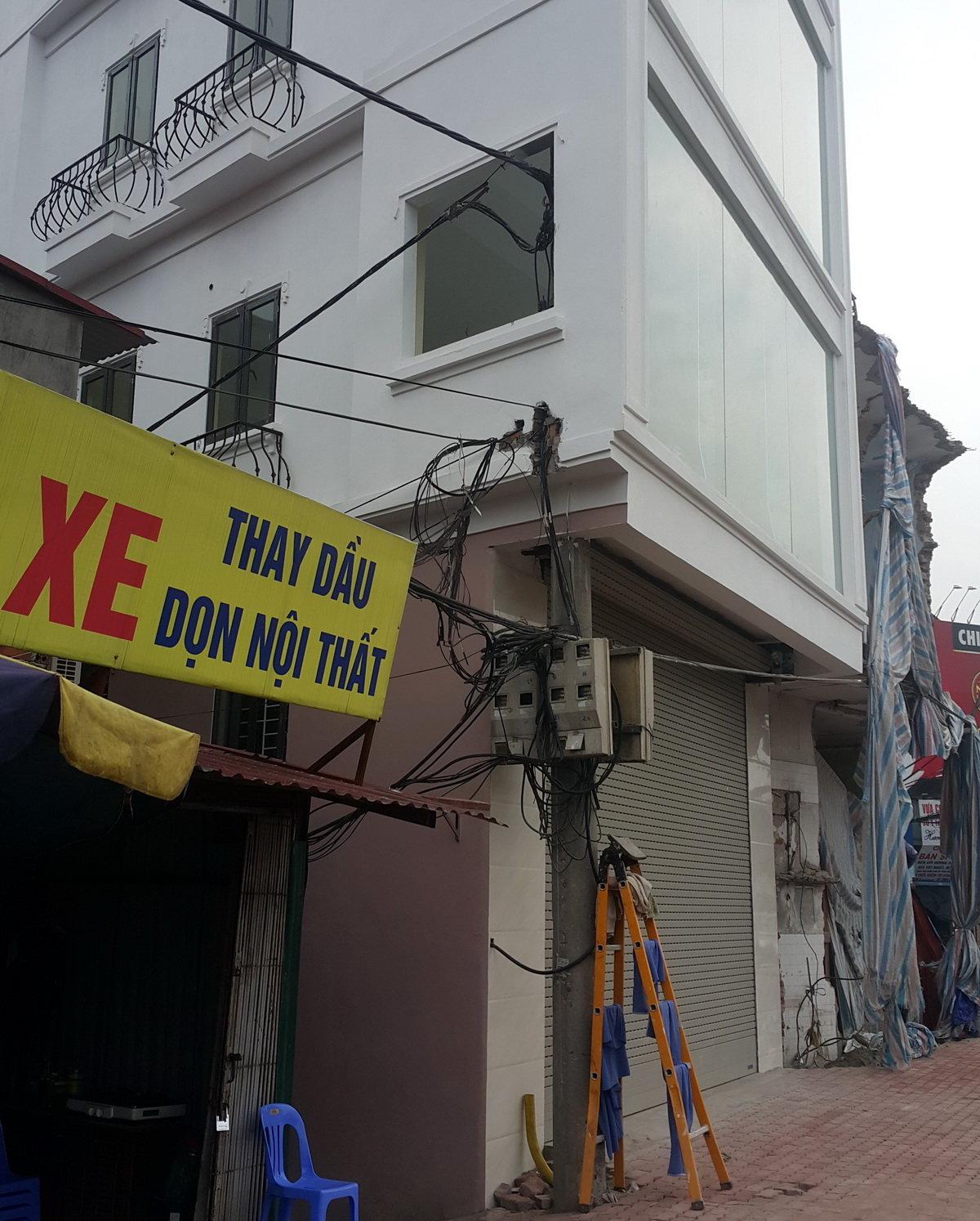Cột điện vẫn đang truyền tải điện được chủ nhà xây tường ôm lại - Ảnh: LÂM HOÀI