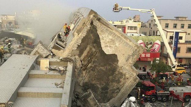 Lực lượng cứu hộ tại hiện trường một tòa nhà bị sập - Ảnh: Reuters