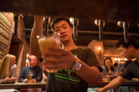Khách hàng hứng thú tự rót bia tại nhà hàng Jing-A Brewing. (Ảnh: NEW YORK TIMES)