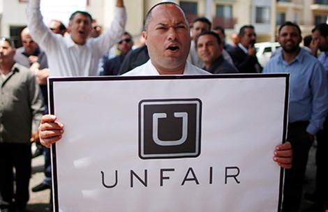 """Một người biểu tình phản đối ứng dụng Uber là """"Không công bằng"""" với các hãng taxi. Ảnh: Reuters"""