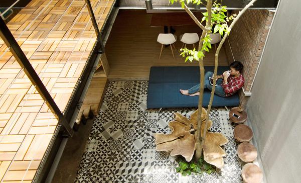Khu vực tiếp khách lạ mắt với bàn ghế gỗ thiết kế độc đáo lấy ý tưởng từ những chiếc thớt. Chiếc ghế sofa xanh hiện đại còn tạo vách ngăn tuyệt đẹp cho phòng khách và bếp.