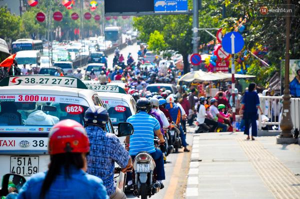 Xe máy và ô tô chen nhau nhích từng chút trên đường.