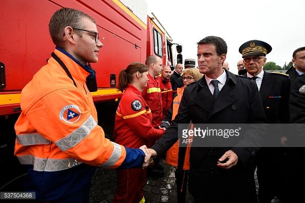 Thủ tướng thăm hỏi nhân viên phòng cháy chữa cháy tại hiện trường. Ảnh: Lionel Bonaventure / AFP