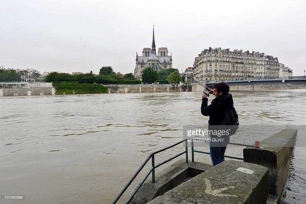 Một anh chàng tranh thủ câu cá lúc nước sông dâng cao. Ảnh: Bertrand Guay/ AFP