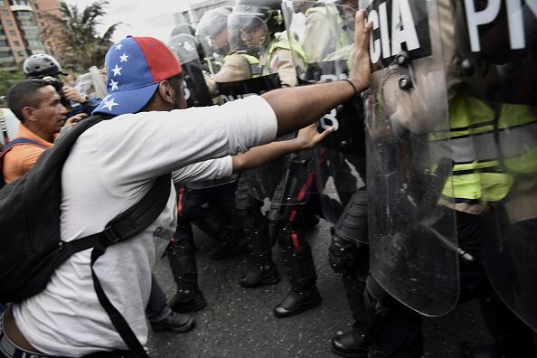 Đụng độ xảy ra giữa người biểu tình và cảnh sát chống bạo động Venezuela. Ở thời điểm hiện tại, người dân quốc gia Nam Mỹ đang phải sống trong cảnh thiếu thốn tới cùng cực. Điện và nước cũng thường xuyên bị cắt. Ảnh: Getty