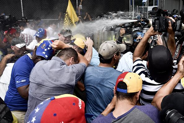 Cảnh sát chống bạo động sử dụng hơi cay để giải tán đám đông biểu tình. Tình trạng khốn cùng của người dân được phe đối lập tận dụng nhằm phát động các cuộc tuần hành chống chính phủ, kêu gọi trưng cầu dân ý lật đổ Tổng thống Maduro. Ảnh: Getty