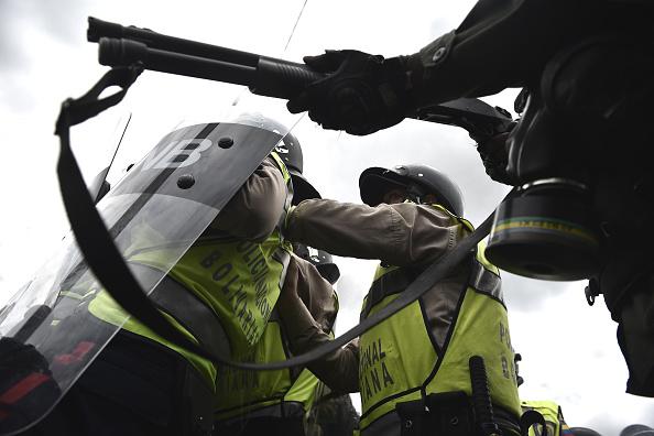 Cảnh sát chống bạo động và lực lượng Vệ binh Quốc gia Venezuela được huy động để giải tán đám đông. Tình trạng lạm phát ở Venezuela đang ở mức cao kỷ lục khi đồng tiền ngày càng mất giá. Các kệ hàng của siêu thị thường xuyên trống trơn vì khủng hoảng nguồn cung. Ảnh: Getty