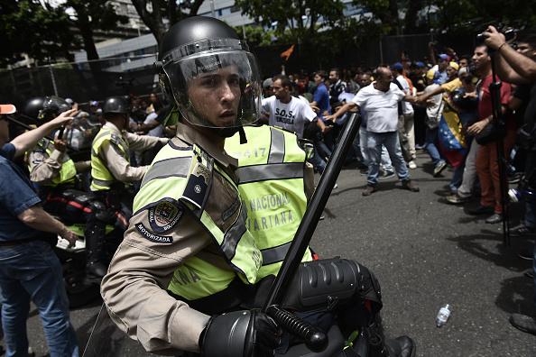 Đụng độ giữa cảnh sát và những người chống chính phủ. Khủng hoảng kinh tế Venezuela được coi là hậu quả của tình trạng giá dầu giảm và bị bên ngoài cô lập. Ảnh: Getty