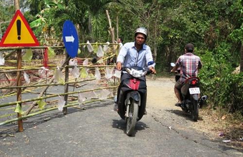 Người dân đi bằng xe máy, xe thô sơ bằng con đường tạm vừa mở.
