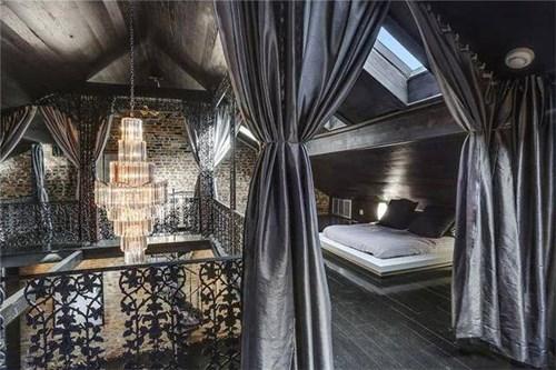 Phòng ngủ ở không gian rộng rãi với đèn chùm và lan can tinh xảo.