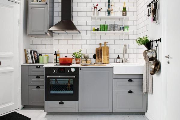 Nhà bếp sạch sẽ với tủ bếp chữ I màu xám và đá ốp tường trắng dễ dàng cho việc lau chùi.