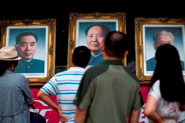 Người dân Trung Quốc đang ngắm ảnh chân dung các nhà lãnh đạo. Từ trái qua, lần lượt là Chu Ân Lai, Mao Trạch Đông và Lưu Thiếu Kỳ
