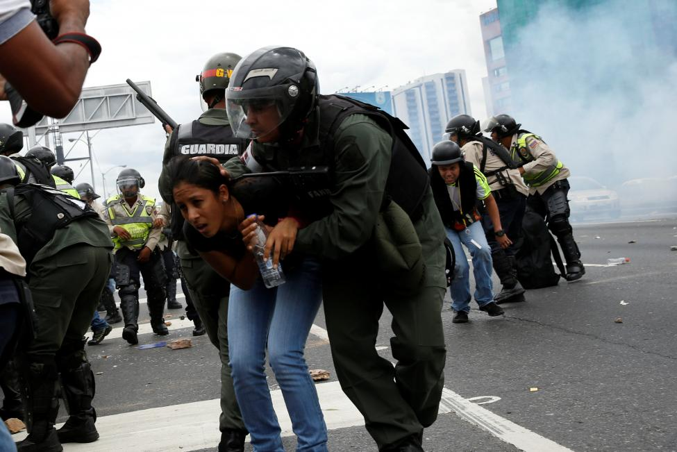 Một phụ nữ được thành viên lực lượng Vệ binh Quốc gia Venezuela đưa khỏi khu vực bị ảnh hưởng bởi hơi cay. Những người biểu tình muốn xông vào Ủy ban Bầu cử Quốc gia nhưng bị ngăn chặn. Ảnh: Reuters