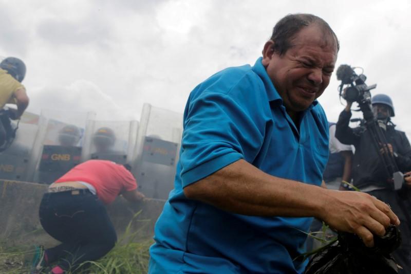 Người biểu tình bỏ chạy vì lựu đạn hơi cay. Henrique Capriles, lãnh đạo phe đối lập, khẳng định, họ sẽ không bỏ cuộc. Ảnh: Reuters