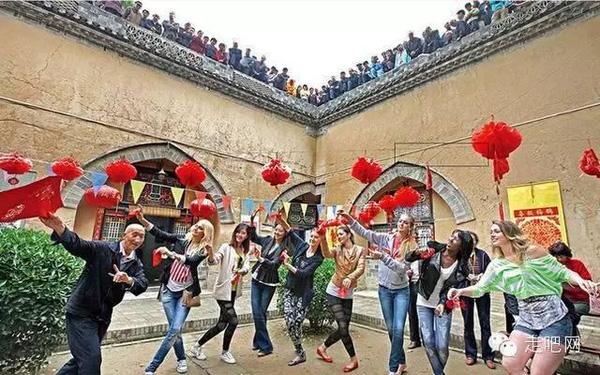 Các du khách tưng bừng nhảy múa bên ngoài mảnh sân chung trong một khu nhà.