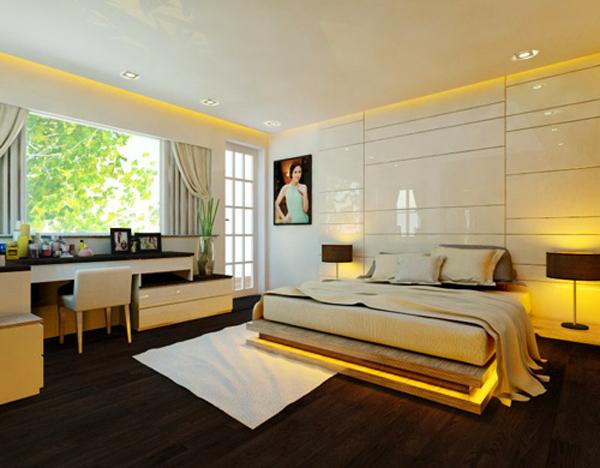Đây là phòng ngủ của hoa hậu Ngọc Hân trong căn nhà sang trọng tại Hà Nội được thiết kế nhẹ nhàng với tông màu trầm. Hệ thống đèn hắt trần vàng dịu nhẹ, ấm áp. Cạnh cửa sổ là chiếc bàn dài đặt đồ trang trí nhỏ xinh và cũng là nơi hoa hậu có thể làm việc hoặc trang điểm.