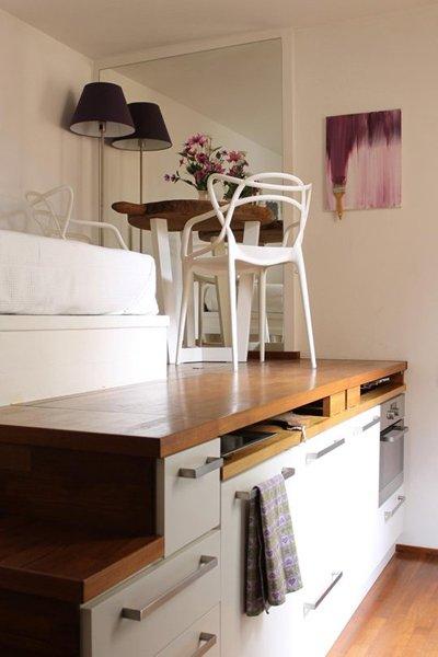Một phần của khối diện tích được sử dụng làm bếp nấu, bồn rửa, lò nướng và ngăn lưu trữ với cánh tủ dạng lật.