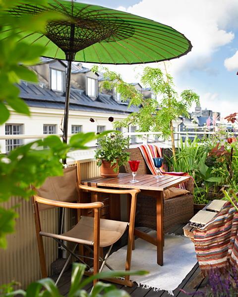 Một chiếc ô màu xanh đặt cạnh bộ bàn ghế uống nước sẽ góp phần mang đến không khí dịu mát, trong lành cho ban công nhà bạn.