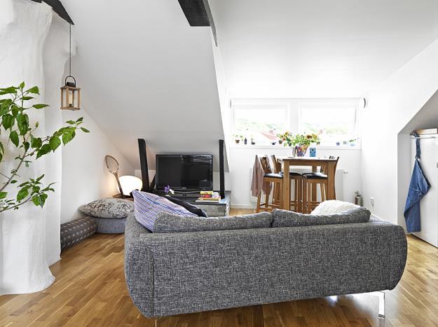 Phòng khách được bố trí vô cùng khoa học với chiếc ghế sofa đặt ở giữa phòng giúp ngăn chia khéo léo khu vực tiếp khách với các khu vực khác. Nơi đặt ti vi được bố trí ở bức tường góc nghiêng nhỏ nhất của căn hộ.