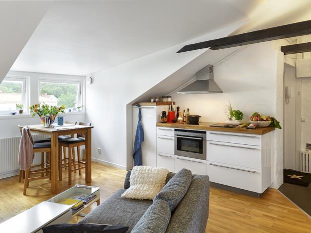 Khu vực nấu nướng và ăn uống của gia đình được đặt ở phía tường nghiêng bên phải lối vào nhà. Khu vực này được thiết kế khá ấn tượng với tủ bếp kiêm bếp nấu. Lò nướng được đặt phía dưới bếp nấu giúp việc nội trợ hàng ngày được tiện lợi hơn.