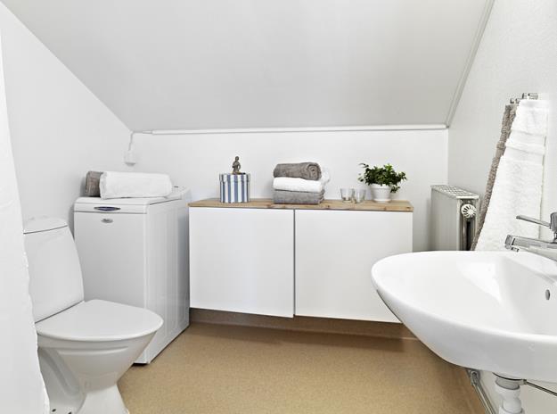 Do hạn chế về trần thấp, nghiêng của áp mái, phòng tắm được chọn hoàn toàn màu trắng để tăng thêm sự thoáng sáng, gọn sạch.