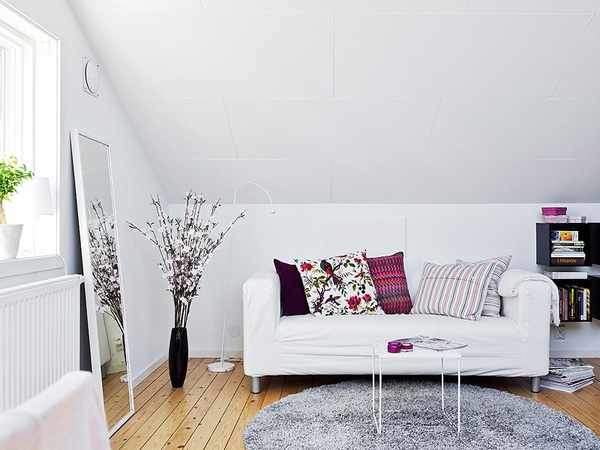 Phòng khách được bài trí vô cùng đơn gian gồm ghế sofa bàn trà mini và những chiếc gối tựa họa tiết vui nhộn.