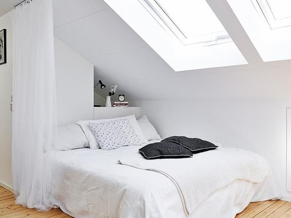 Một phòng ngủ khiêm tốn được bố trí tại một góc phòng và được ngăn cách với các không gian khác bởi tấm rèm trắng.