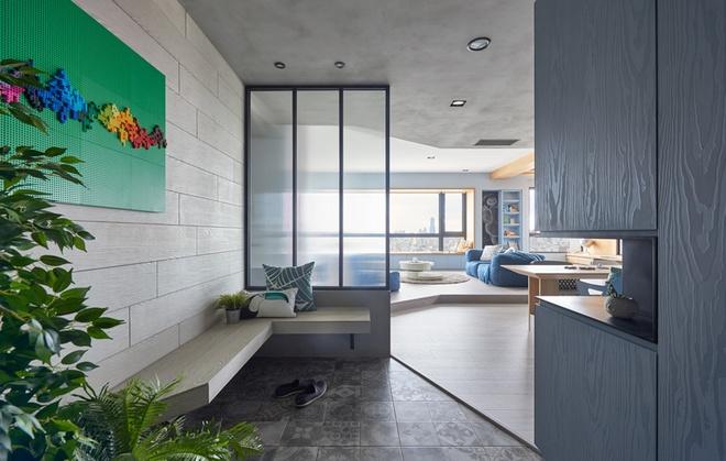 Lối vào căn hộ được bài trí với một chiếc ghế băng dài cùng với cây xanh. Trên bức tường là bức trang trí ghép từ Lego nhiều màu sắc.