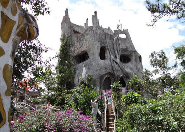 Được xây dựng từ năm 1990, Ngôi nhà điên nổi tiếng vì kiến trúc độc đáo đến quái dị, với vẻ bề ngoài trông như những gốc cây, hang động giữa rừng già, hoặc một phần cơ thể của những con thú hoang dã.